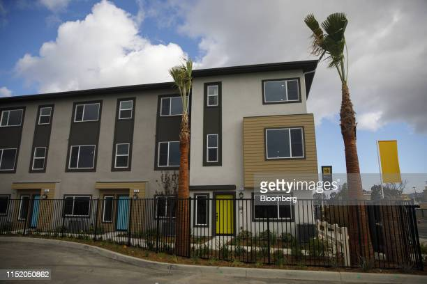 Palm trees stand in front of new homes at the KB Home Cottages at Harbor Pointe development in Harbor City, California, U.S., on Friday, June 21,...
