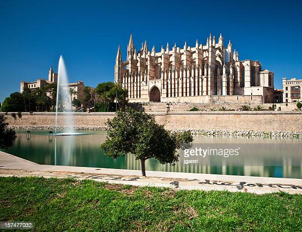 palma cathedral from across a pool with a fountain  - palma majorca stock photos and pictures