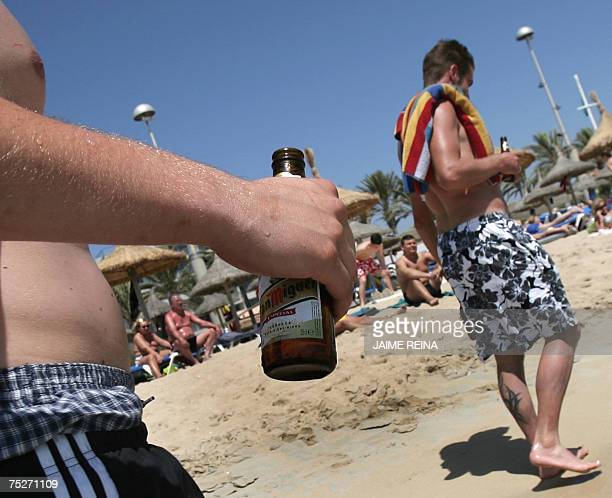 Two German tourists walk with a bottle of beer on Arenal Beach in Palma de Mallorca Balearic Island Spain 06 July 2007 Hundred thousands of Germans...
