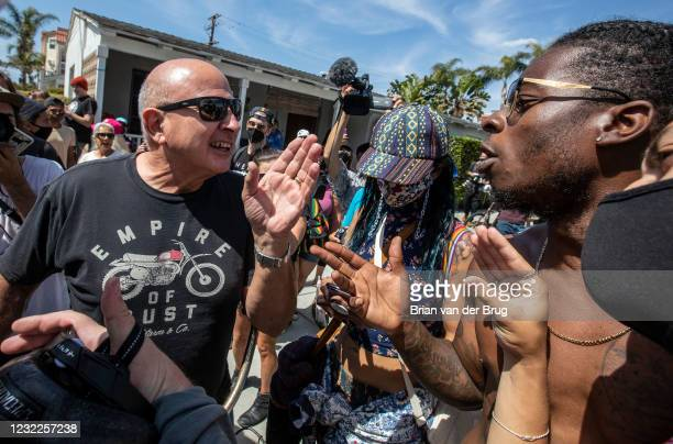 Palmdale resident Josiah Mokelu right, argues with a Huntington Beach resident who would not be identified, left, as protesters gather to demonstrate...