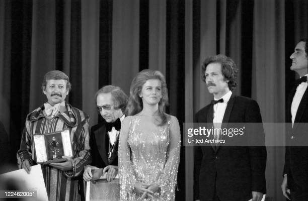 Palme d'Or for the Algerian film director Mohammed LakhdarHamina on stage with actress AnnMargret German director Werner Herzog and actor Vittorio...