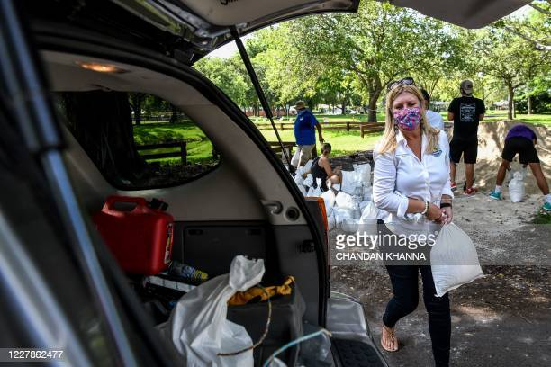 Palmetto Bay's Mayor Karyn Cunningham, puts sand bags in a resident's car trunk in Palmetto Bay near Miami, on July 31, 2020 as Floridians prepare...