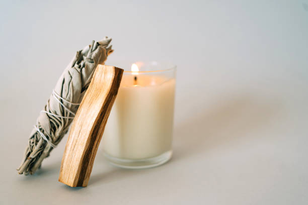 Palo Santo stick, White Sage and burning candle on gray background. Set for aromatherapy and rituals. Copy space for your design. Front view and close-up