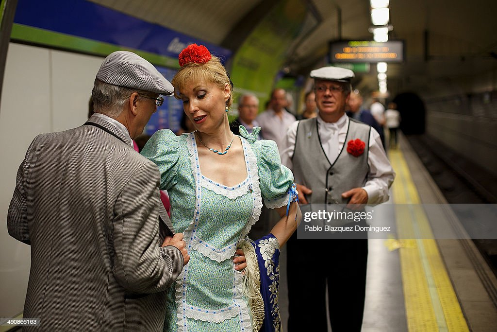 Paloma Clemente (2L) dance a 'chotis' with her husband Agustin Torres (L) during the San Isidro festivities as they wait for the train on their way to Pradera de San Isidro park on May 15, 2014 in Madrid, Spain. During the festivities in honor of San Isidro Labrador in Madrid revelers take the streets and enjoy music and popular food. Chulapos or Goyescos dance the regional dance known as 'chotis' wearing traditional costumes of Madrid.