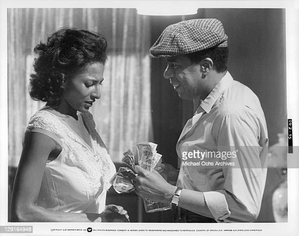 Pam Grier And Richard Pryor counting money in a scene from the film 'Greased Lightning' 1977