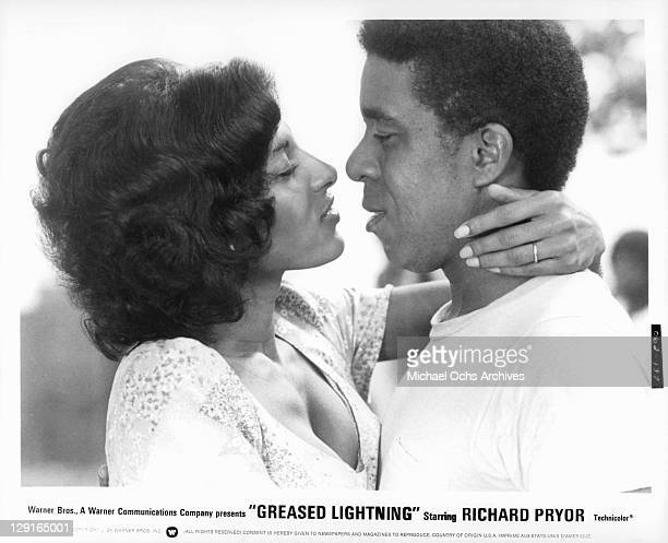 Pam Grier And Richard Pryor embrace to kiss in a scene from the film 'Greased Lightning' 1977