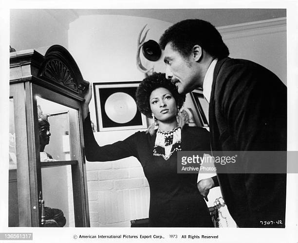 Pam Grier resting her hand on a wooden display case while William Marshall is staring mesmerized of what he sees inside the case in a scene from the...