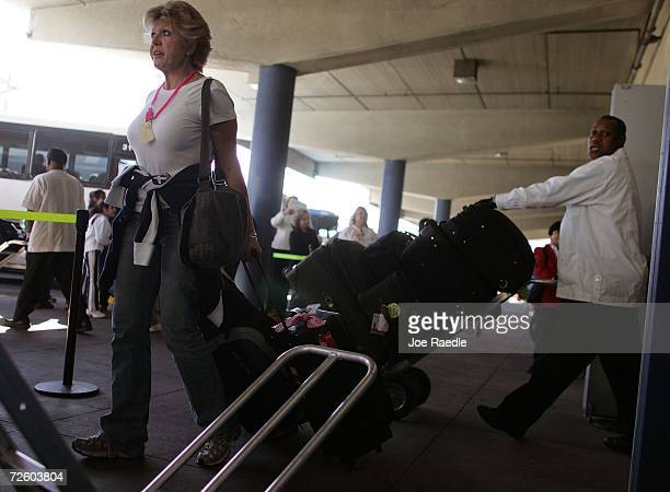 Pam Stupnik from Pueblo Colorado walks with her luggage after disembarking from the Carnival Liberty Cruise ship at Port Everglades on November 19...