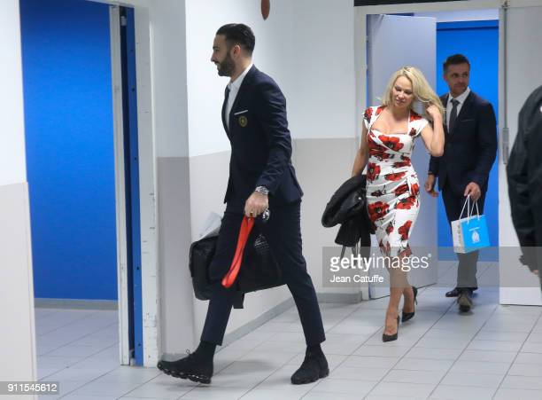 Pamela Anderson and Adil Rami of OM leave the stadium following the French Ligue 1 match between Olympique de Marseille and AS Monaco at Stade...