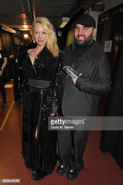 Pamela Anderson and Michael Halpern winner of the British Emerging Talent Womenswear award for Halpern pose backstage at The Fashion Awards 2017 in...