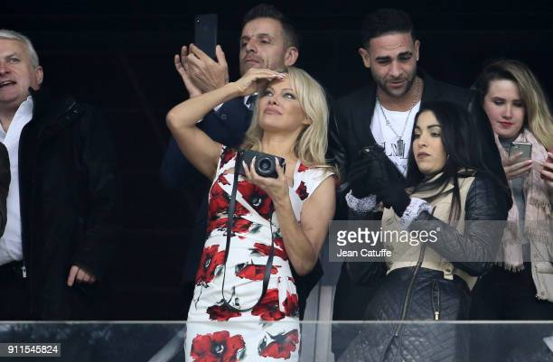 Pamela Anderson enjoys the arrivals of paratroopers on the pitch before the French Ligue 1 match between Olympique de Marseille and AS Monaco at...