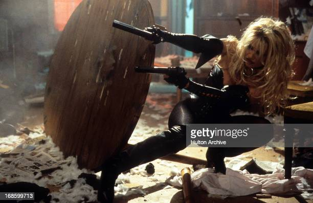 Pamela Anderson firing guns from behind table in a scene from the film 'Barb Wire' 1996