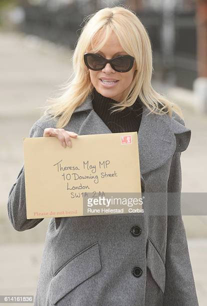 Pamela Anderson holds up an envelope as she urges Theresa May to ban wild animal circuses in the UK on October 11 2016 in London England