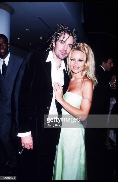 Pamela Anderson Lee stands with husband Tommy Lee at PETA's Milennium Gala September 18 1999 at Paramount Studios in Los Angeles California Lee got...