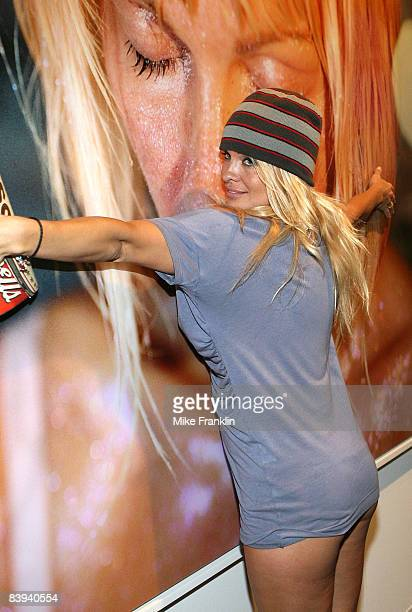Pamela Anderson poses near a photograph of herself at Art Basel Miami Beach on December 6, 2008 in Miami Beach, Florida.