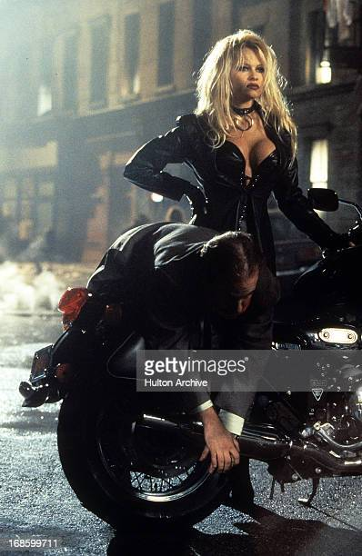 Pamela Anderson with bound man on her motorcycle in a scene from the film 'Barb Wire' 1996