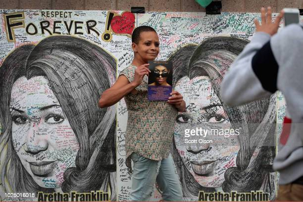 Pamela Bolton poses for pictures next to posters of Aretha Franklin created by artist Mark Gaines outside of the Charles H Wright Museum of...