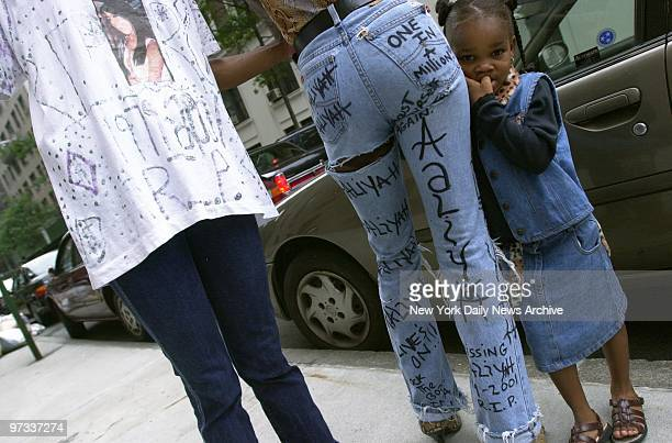 Pamela Deckard and Shanti Gunn wear their tributes to Aaliyah as Gunn's daughter Amani Davis looks on outside St Ignatius Loyola Roman Catholic...