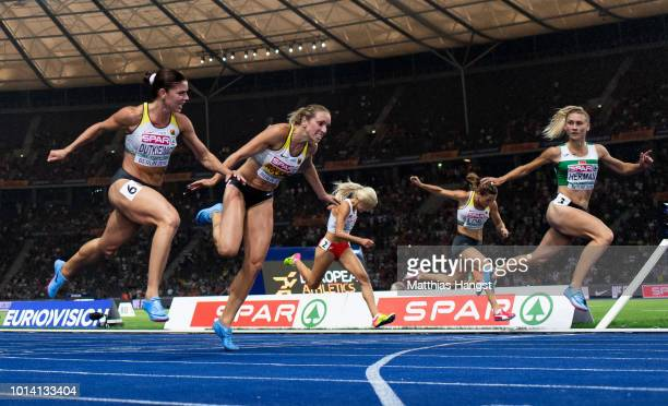 Pamela Dutkiewicz of Germany, Cindy Roleder of Germany and Elvira Herman of Belarus cross the finish line in the Women's 100m Hurdles Final during...