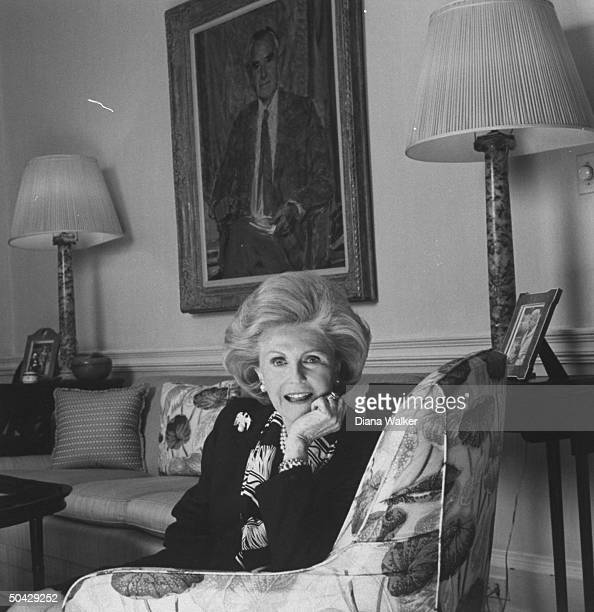 Pamela Harriman sitting in a chair at home a portrait of her late husband politician Averell Harriman is in the bkgrd Georgetown