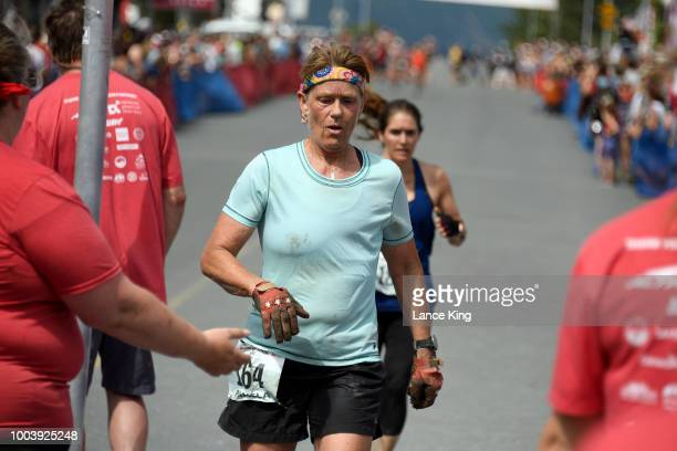 Pamela Richter reacts after crossing the finish line during the Women's Division of the 91st Running of the Mount Marathon Race on July 4 2018 in...