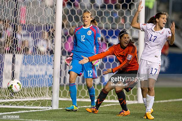 Pamela Tajonar and Kenti Robles of Mexico react along with Tobin Heath of the United States after a second ball was thrown on the field in the first...