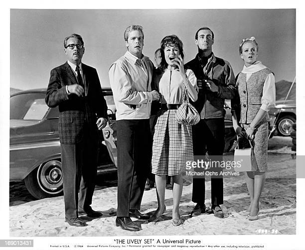 Pamela Tiffin and Doug McClure standing with three other all with a look of shock on their faces in a scene from the film 'The Lively Set', 1964.