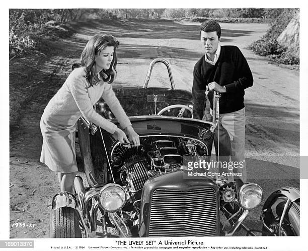 Pamela Tiffin and James Darren dealing with car issues on the side of the road in a scene from the film 'The Lively Set', 1964.