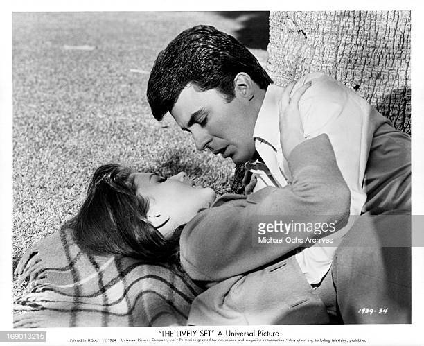 Pamela Tiffin and James Darren gazing into one an other eyes with passion while laying under a tree in a scene from the film 'The Lively Set', 1964.
