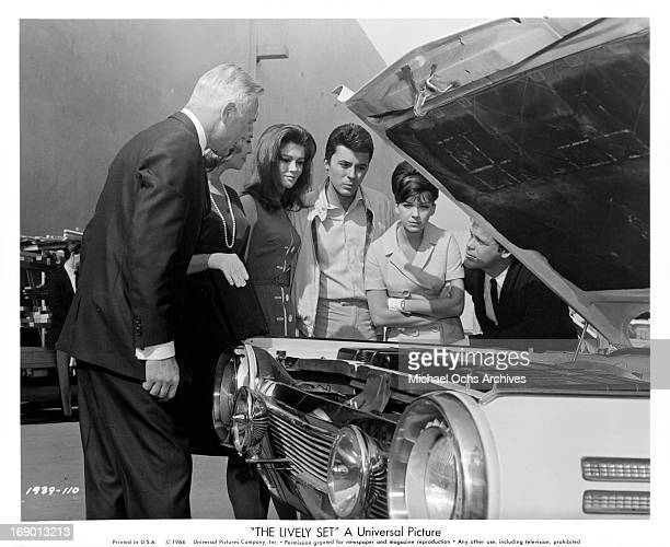 Pamela Tiffin and James Darren listen to the explanation of the engines features and benefits in a scene from the film 'The Lively Set', 1964.