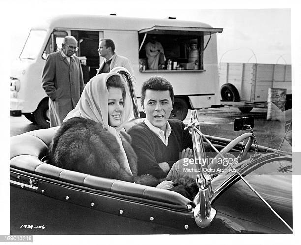 Pamela Tiffin and James Darren sitting in a car together in a scene from the film 'The Lively Set', 1964.