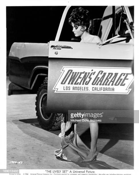 Pamela Tiffin changes her clothes behind a car door in a scene from the film 'The Lively Set', 1964.