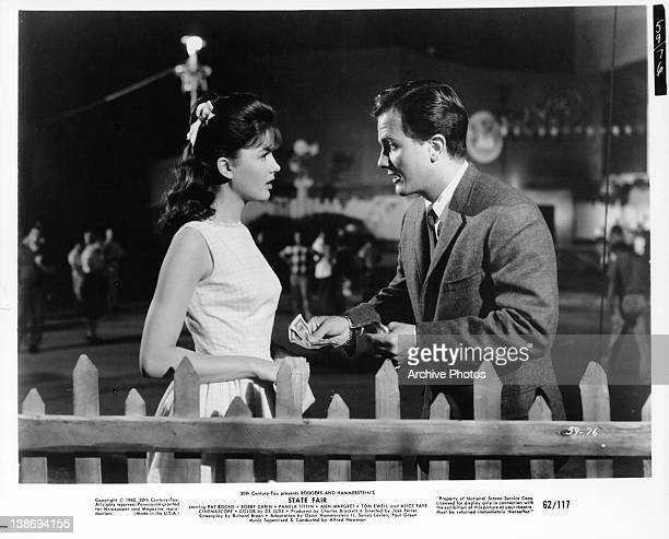 Pamela Tiffin looking at Pat Boone as he offers her money in a scene from the film 'State Fair', 1962.