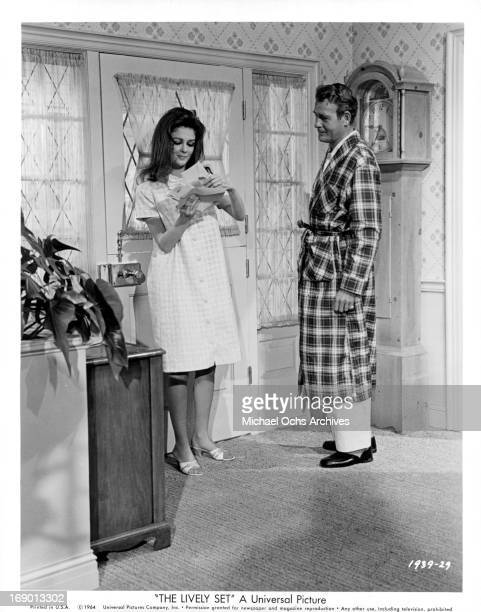 Pamela Tiffin searches for a letter as Charles Drake watches in a scene from the film 'The Lively Set', 1964.