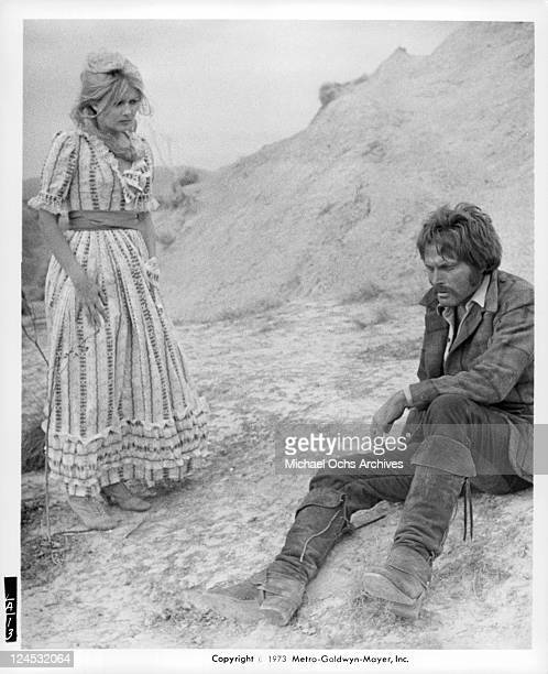 Pamela Tiffin stands talking to Franco Nero who sitting in a scene from the film 'Deaf Smith And Johnny Ears' 1973