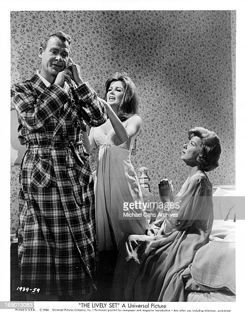 Pamela Tiffin tries to get Charles Drake's attention while he is on the telephone in a scene from the film 'The Lively Set', 1964.