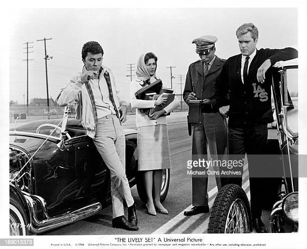 Pamela Tiffin watches as James Darren and Doug McClure receive traffic citations in a scene from the film 'The Lively Set', 1964.