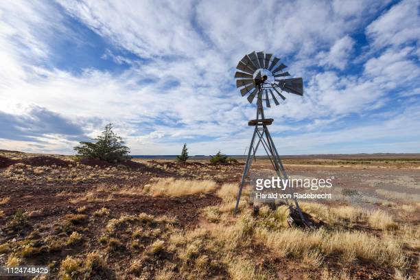pampa with old windmill on a farm in bosques petrificados de jaramillo national park, patagonia, argentina - pampa stock-fotos und bilder