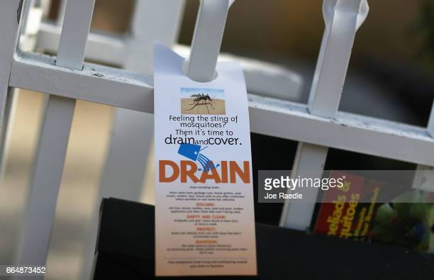 A pamphlet educating people about mosquitos hangs on a fence as workers with MiamiDade County mosquito control department inspect a neighborhood for...