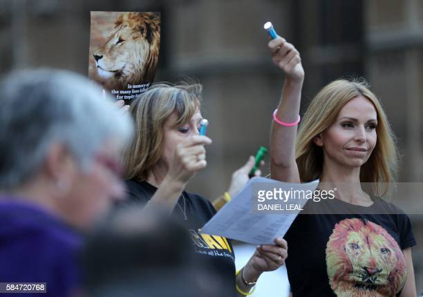 A pamphlet is held up showing an image of Cecil the lion as people wave torches at a vigil in central London on July 30 2016 Cecil was killed by...