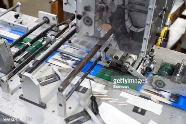 Pamphlets move along a conveyor belt as a machine applies stickers at the Holmes Finishing House printing and binding facility in Markham Ontario...
