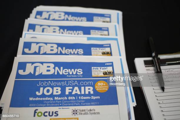 Pamphlets sit stacked on a table during a Job News USA career fair in Overland Park Kansas US on Wednesday March 8 2017 Applications for US jobless...