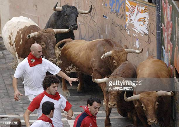A local runner who was resulted gored in the leg moments later runs next to Cebada Gago fighting bulls on Estafeta Street 10 July 2006 during the...