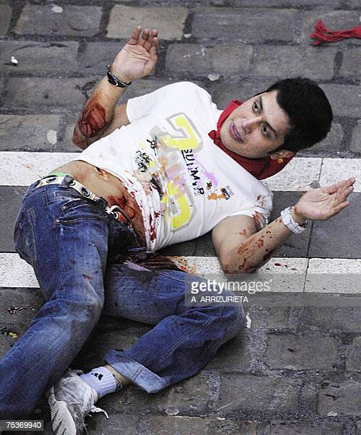 A runner is covered with blood after being gored by a Marques de Domecq fighting bull during the 6th day of the San Fermin bull run 12 July 2007 in...