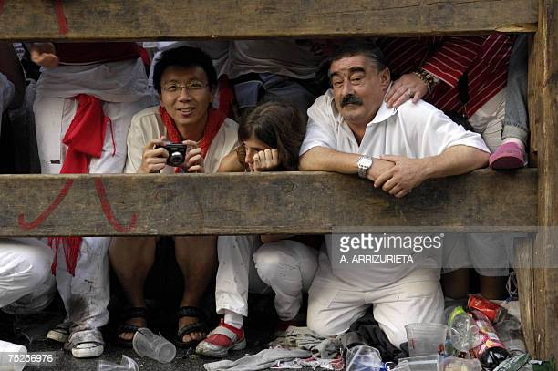 From a wooden fence local residents and tourists view participants and bulls during the first day San Fermin bullrun 07 July 2007 in Pamplona...