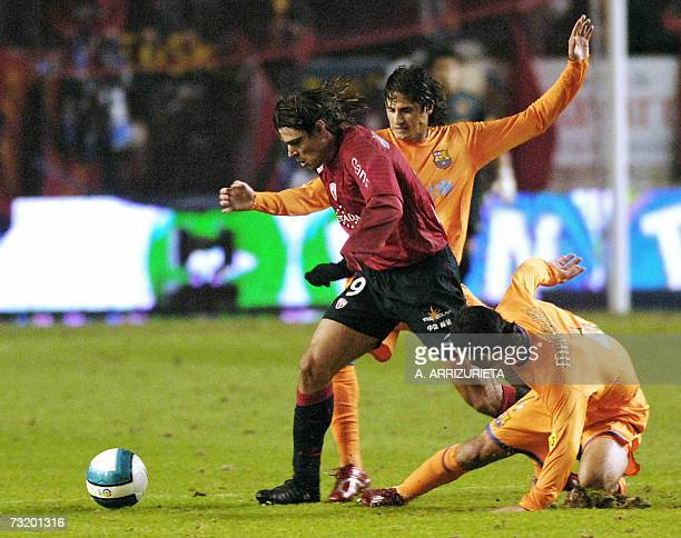 Osasuna's Serbian player Savo Milosevic fights for the ball with Barcelona's Brazilian player Edmilson Gomes de Moraes and Mexican player Rafael...