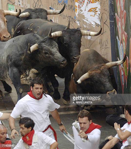 Runners and Miura fighting bulls run past the Estafeta turn during the third encierro of the San Firmin fair 09 July 2006 in Pamplona north of Spain...