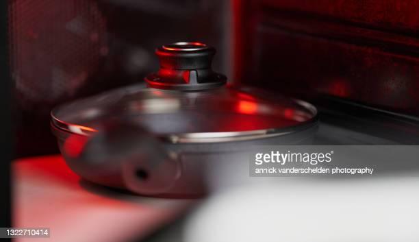 pan and lid in oven - annick vanderschelden stock pictures, royalty-free photos & images