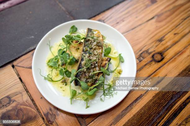 pan fried fish on rustic wooden background - mackerel stock pictures, royalty-free photos & images