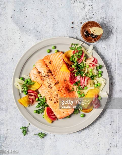 pan fried salmon with vegetables on gray background - salmon seafood stock pictures, royalty-free photos & images